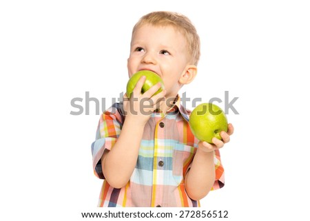 Beautiful happy smiling joyful child (little boy) eating healthy food (green apples) and looking up  isolated on white background