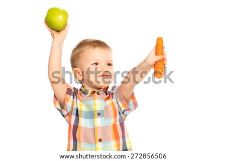 Beautiful happy smiling joyful child (little boy) eating healthy food (green apples, carrot) and looking up  isolated on white background - stock photo