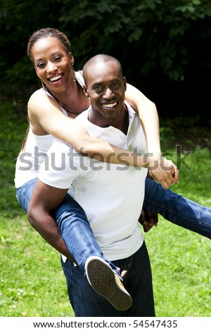 Beautiful happy smiling laughing African American couple piggyback playing in the park, woman hugging man, wearing white shirts and blue jeans. - stock photo