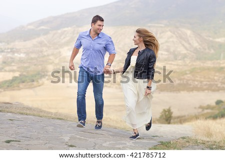 Beautiful happy smiling running couple in love outdoors