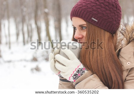 Beautiful Happy Smiling Winter Woman with Mug Outdoor. Smiling Girl Outdoors with Hot Drink