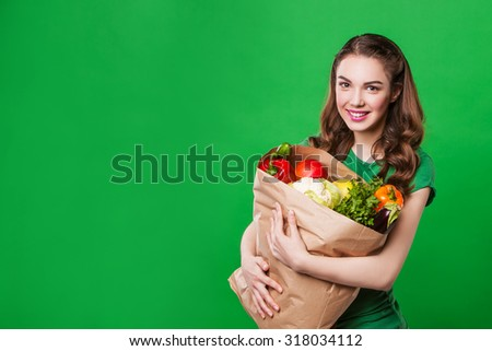 beautiful happy smiling woman holding a grocery bag full of fresh and healthy food on green background