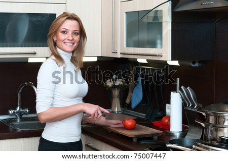 Beautiful happy smiling woman in kitchen interior cuts a tomato on a cutting board. One person only