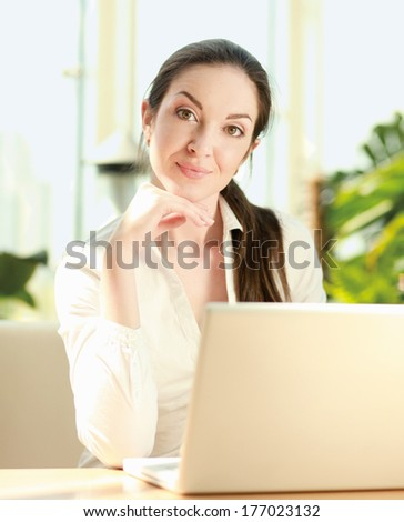 Beautiful happy smiling woman sitting on the sofa with laptop