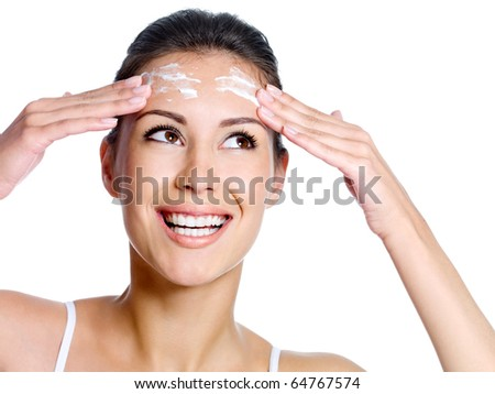 Beautiful happy smiling woman with cream on the forehead of her face looking up - isolated - stock photo
