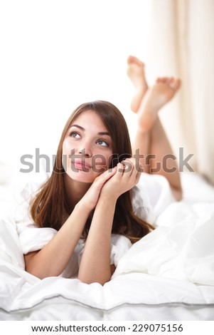 Beautiful happy smiling young woman in bed, isolated
