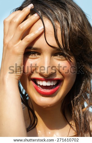 Beautiful happy tanned young woman outdoor in summer sun. Wet skin and hair covered in water. Red lipstick and natural makeup.
