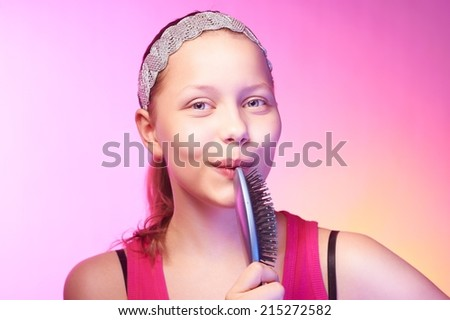 Beautiful happy teen girl uses hairbrush like a microphon - stock photo