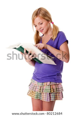 Beautiful happy teenager school girl pointing in books to read and learn, standing and smiling, isolated.