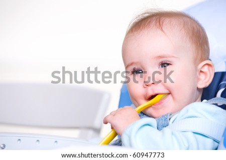 Beautiful happy toddler with spoon sitting on chair - stock photo
