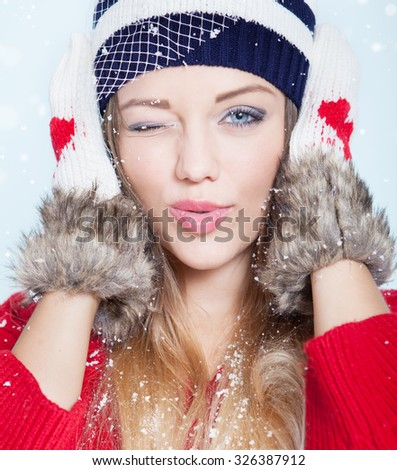 Beautiful happy winking young woman wearing winter hat and gloves covered with snow flakes. Christmas portrait concept. - stock photo