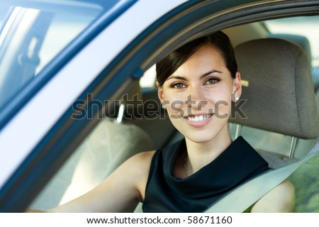 Beautiful happy woman driving her car - stock photo