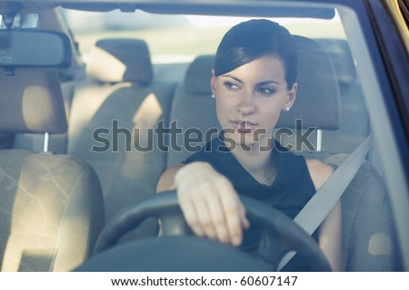 Beautiful happy woman driving her car in the evening. Windshield view - stock photo