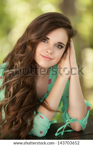 Beautiful happy woman girl smiling outdoors in green summer nature. Pretty woman with natural makeup curly hairstyle in country village in park. Attractive beauty Healthy girl. healthy life concept