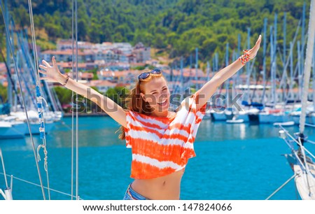 Beautiful happy woman having fun in yacht port, cute girl enjoying luxury sailing cruise, relaxation on the beach, active lifestyle, summer adventure concept - stock photo