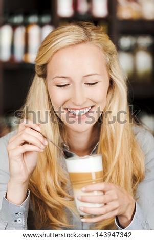 Beautiful happy woman holding coffee mug at cafe - stock photo