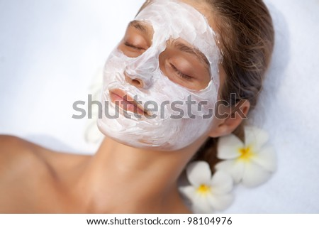 Beautiful happy woman in a tropical spa making face mask treatment - stock photo