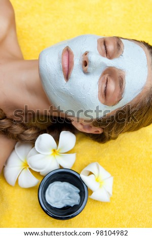 Beautiful happy woman in a tropical spa making face mask treatment