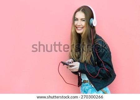 beautiful happy woman in headphones listening music near the wall - stock photo