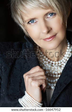 beautiful happy woman in her mid 40s with blond short hair wearing fresh water pearls - stock photo