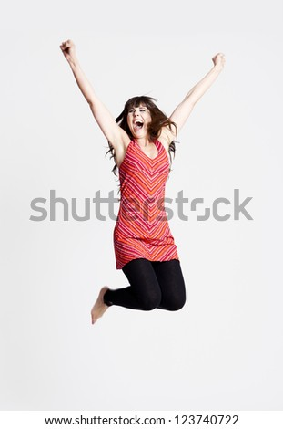 Beautiful happy woman jumping over a grey background