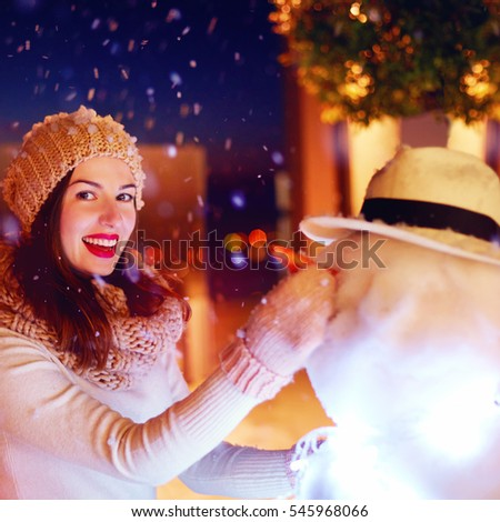 beautiful happy woman making snowman under magical winter snow