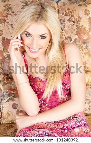 Beautiful happy woman on a sofa making a phone call . - stock photo