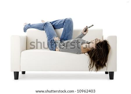 Beautiful happy woman on a white sofa making a phone call - stock photo