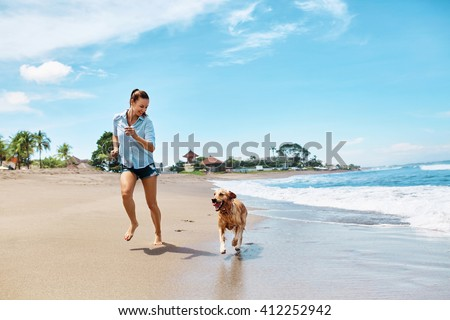 Beautiful Happy Woman Running With Her Dog, Golden Retriever On Wet Sand On The Beach By Sea. Girl Enjoying Summer Holidays Vacations, Having Fun With Her Pet. Summertime Concept. - stock photo