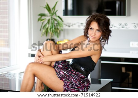 Beautiful happy woman sitting on a table in the kitchen
