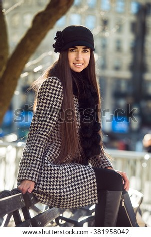 Beautiful happy woman sitting on the bench at spring sunny day wearing fashionable coat and hat