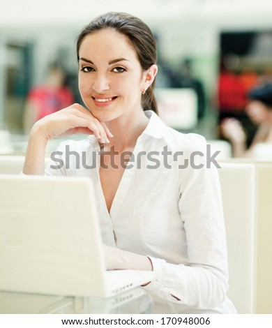 Beautiful happy woman sitting with laptop