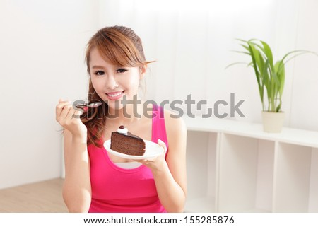 beautiful happy woman smiles eating chocolate cake at home, asian beauty model - stock photo