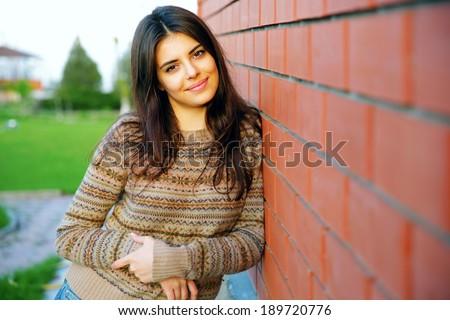 Beautiful happy woman standing near brick wall - stock photo