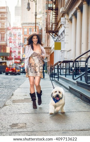 Beautiful happy woman walking with a dog at the street of New York City - stock photo
