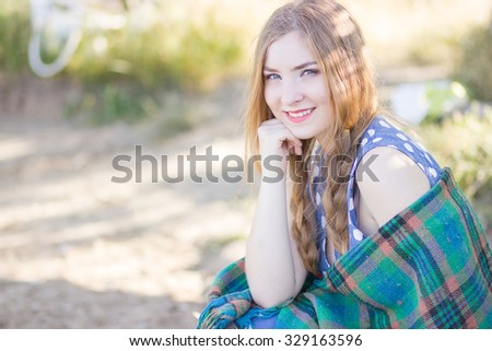Beautiful happy woman with long hair on the nature, covered blanket. Soft focus