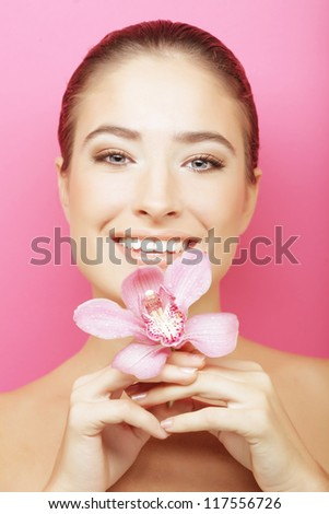 Beautiful happy woman with orchid flower over pink background - stock photo