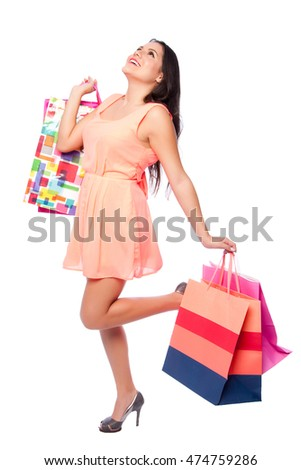 Beautiful happy woman with shopping bags on shoppingspree standing cute with leg looking up, consumer lifestyle concept.