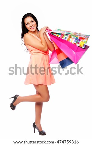 Beautiful happy woman with shopping bags on shoppingspree standing cute with leg up, consumer lifestyle concept.