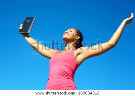 Beautiful happy young african american female celebrating success with a Bible against cloudy sky. With arms up praising God. Horizontal Shot. - stock photo