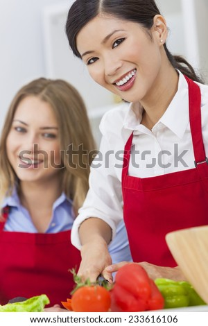 Beautiful happy young Asian Chinese woman or girl and her friend or work colleague wearing a red apron cutting & preparing fresh vegetable salad food in a kitchen - stock photo