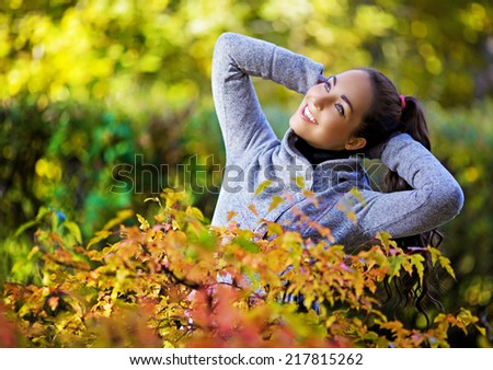 beautiful happy young brunette woman having a walk in the autumn park - stock photo