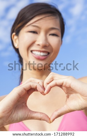 Beautiful happy young Chinese Asian woman or girl in a pink bikini making a heart shape symbol with her hands - stock photo