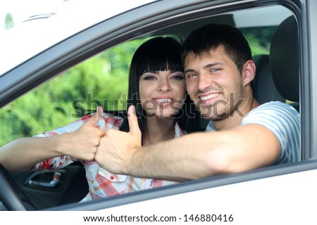 Beautiful happy young couple driving car