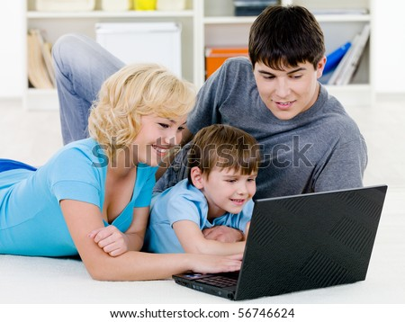 Beautiful happy young family with little son looking in laptop together - indoors - stock photo