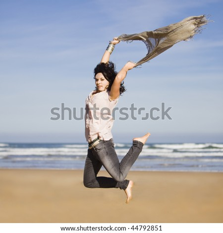 beautiful happy young girl running and jumping over a windy beach with a blowing scarf - stock photo
