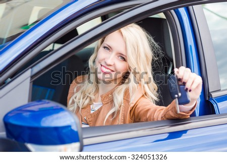 Beautiful happy young girl sitting in her car showing car key