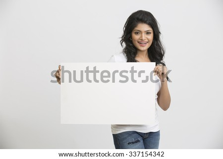 Beautiful happy young Indian woman holding a blank billboard white background - stock photo