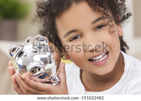 Beautiful happy young mixed race interracial African American female girl child smiling and holding a silver young saver piggy savings money bank - stock photo