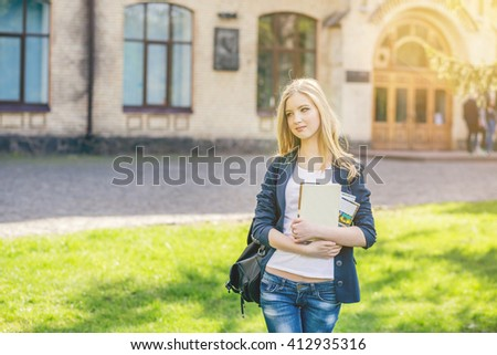 Beautiful, happy young student girl holding book standing on green grass under the tree near the campus, university, school, education. Summer, spring green park - stock photo